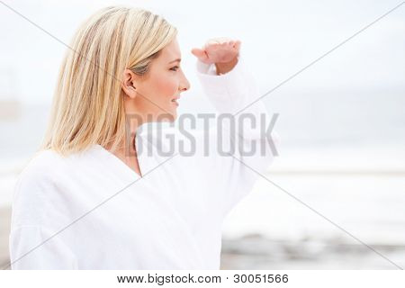 attractive young woman in bathrobe looking into distance in the morning