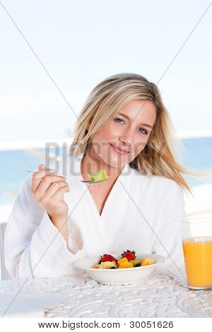 pretty young woman eating breakfast with sea view in background