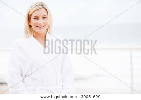 beautiful young woman in bathrobe at home in the morning