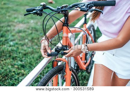 Close-up Girl Hand Lock With Digital Cipher. Woman Summer Stands Bicycle Locking Bicycle With Cable.