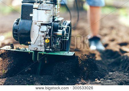 Close Up Photo Of Gardener Cultivate Ground Soil Rototiller , Tiller Tractor, Cutivator, Miiling Mac