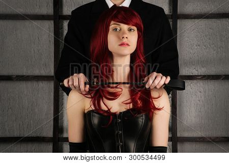 Adult Sex Games. A Man Holds A Spank Near The Neck Of A Red-haired Girl In A Leather Corset. Bdsm Ou
