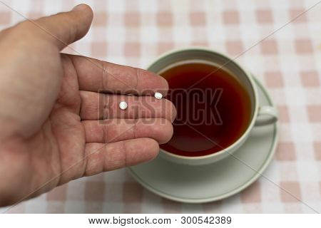 Two Small Sweetener Tablets, Replacing Two Teaspoons Of Sugar In Hand For Adding To A Cup Of Tea