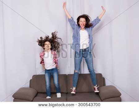 Happy Family Celebrating Mothers Day. Happy Mother And Daughter Jumping On Sofa. Mother And Child En