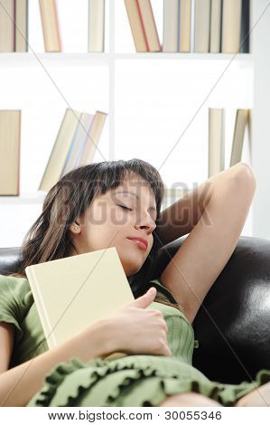Young Woman Is Sleeping On A Sofa In The Living Room With A Book , Bookshelf On Background