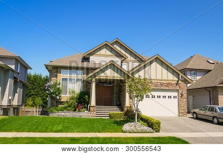 Luxury Family House With Car Parked On Concrete Driveway. Residential House With Landscaped Front Ya