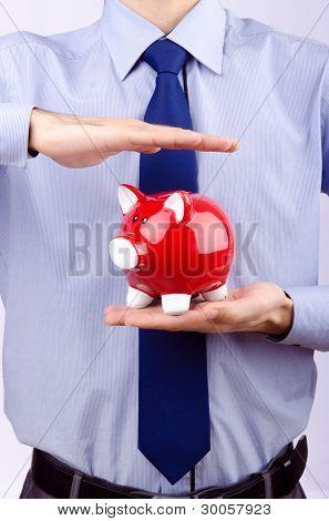 Man saving his money in the piggybank