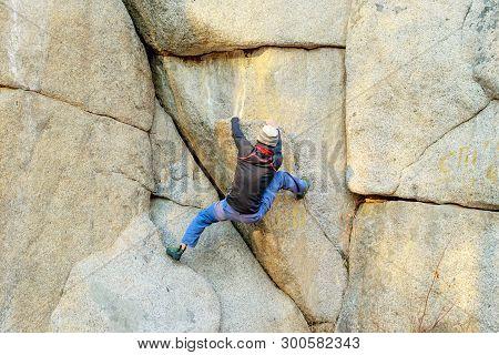 Rock Climber Climbs A Boulder Over A Rock Without Insurance