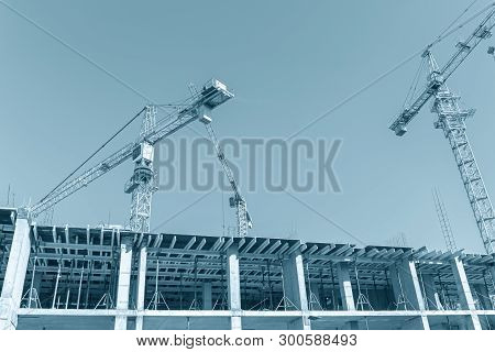 City Construction Site. Building Cranes Against Blue Sky Background. Urban Infrastructure Developmen