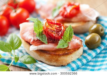 Close up of grilled bread with parma ham and sundried tomatoes
