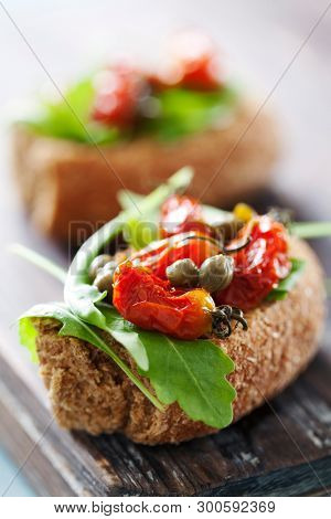 Whole grain rusk with rocket and sundried tomatoes
