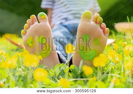 Child Lying On Green Grass. Kid Having Fun Outdoors In Spring Park. Child Feet With Painting Smiles
