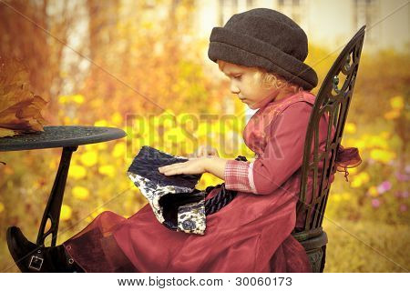 Cute little girl having a rest at a park. Retro style.
