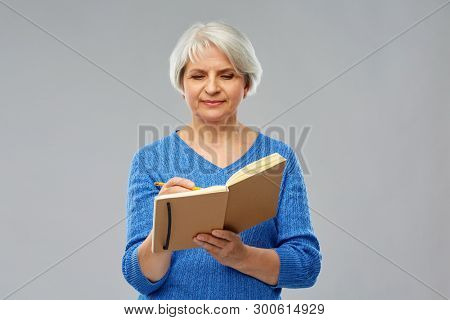 planning and old people concept - portrait of smiling senior woman in blue sweater writing to diary or notebook with pencil over grey background