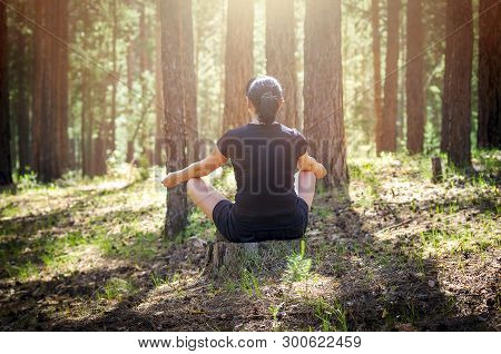 Relaxed Woman Sitting In A Comfortable, Upright Position And Practicing Meditation In The Summer For