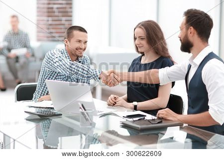 Handshake Business People Sitting At The Office Desk.