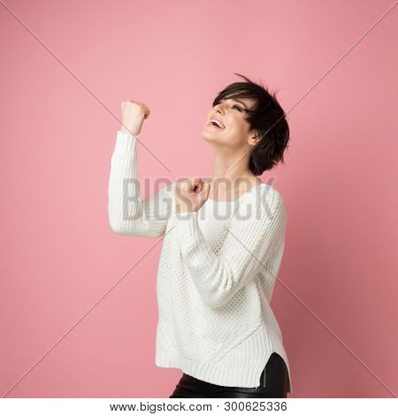 Beautiful young woman happy and excited expressing winning gesture. Successful and celebrating victory, triumphant, studio shot over pink background
