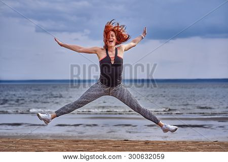 A Middle Aged Woman With Red Hair Emotionally Makes The Jump. A Woman Practices Gymnastics On The Sa