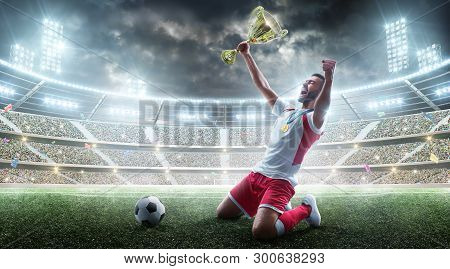 Professional Soccer Player Celebrates Winning The Open Stadium. Soccer Player Holds A Trophy. Medal