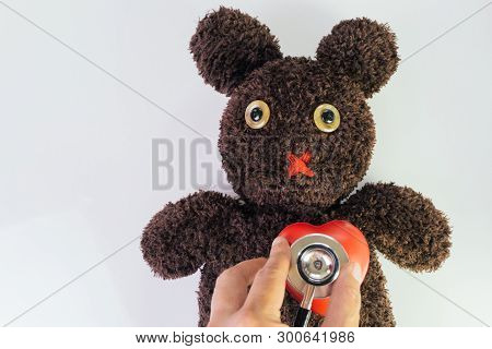 Doctor's Hand Holding Stethoscope Put On Red Heart On Cute Brown Handmade Fluffy Doll With Pitty Eye