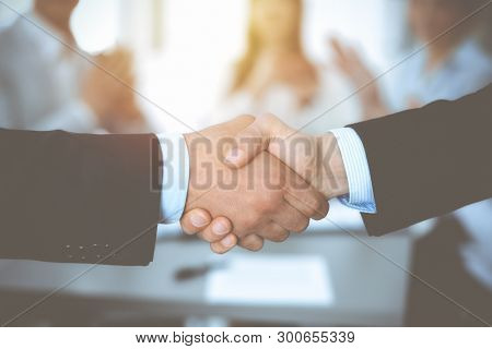Business People Shaking Hands At Meeting While Theirs Colleagues Clapping And Applauding. Group Of U