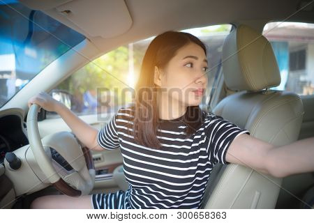 Young Asian Woman Driving Car Keeps Wheel Turning Around Looking Back Over Shoulder Check Behind Goi