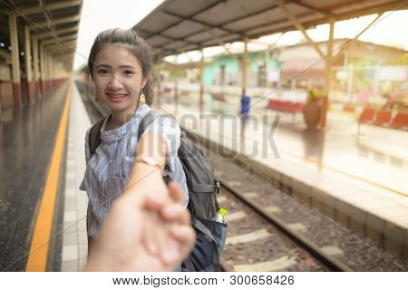 Young Happy Woman Holding Man Hand Leading At Train Station. Couple In Love On Holiday.  Asian Girl