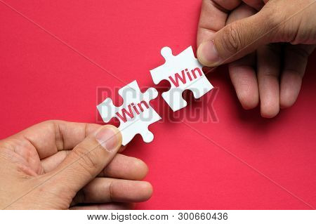 Hand Putting Two Pieces Puzzle Together With Word Win Win Situation