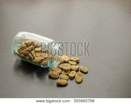 Broad Beans (vicia Faba) Are Poured From A Glass Jar On Brown Wooden Surface.  Broad Beans (vicia Fa