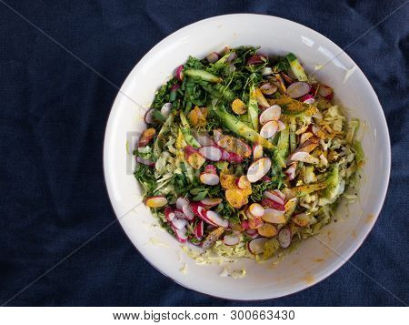Top View On Bowl With Ingredients For Spring Vegetables Salad Standing On Wrinkly Bluish Cotton Fabr