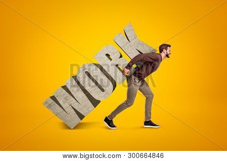 Young Man In Casual Clothes Carrying Heavy Work Sign On His Back On Yellow Background