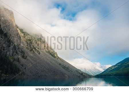 Giant Cloud Above Mountains With Trees In Sunlight. Amazing Mountain Lake. Mountain Range Under Blue