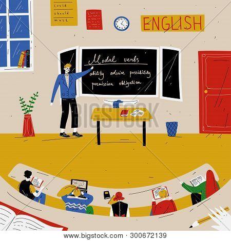 English Lesson. Teacher Near Blackboard In Classroom.