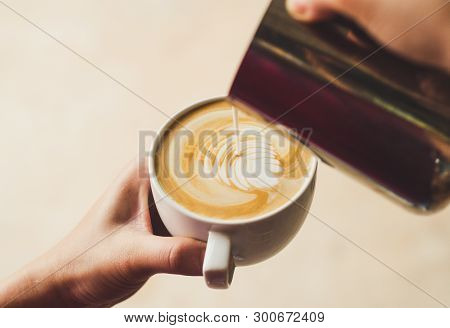 Closeup Image Of Female Barista Holding And Pouring Milk For Prepare Cup Of Coffee, Latte Art, Vinta