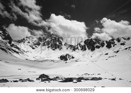 Plateau In High Snowy Mountains With Frozen Lake Covered Snow And Cloudy Sky At Sunny Spring Day. Tu