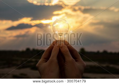 Burning Light Bulb In Hands Against The Sky. The Concept Of The Idea .