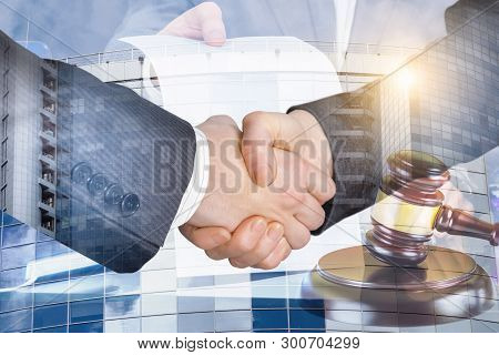 The Handshake Of The Lawyers And The Judges Gavel On Blurred Background.