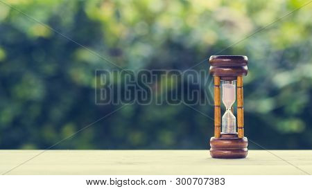 The Time Concepts. Hourglass On Wooden Table With Green Nature Background And Space At The Left. Bus