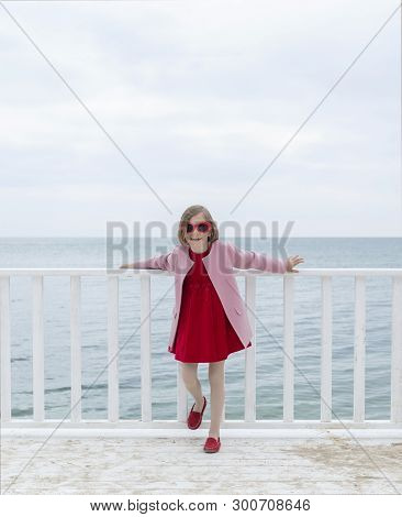 Little Funny Girl (7 Years Old) In A Pink Coat And Red Dress, Laughs, Dances And Sings On A White Wo