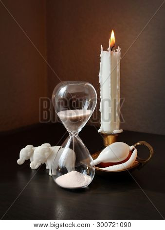 Still Life With Vintage Sandglass, Two Small Toy Elephants, White Shell And Burning Candle Against A