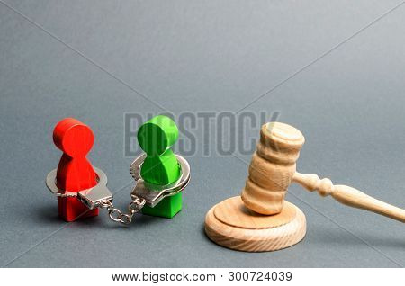 Two People Are Handcuffed To Each Other And Stand Near The Judge's Gavel. Dispute Resolution Through
