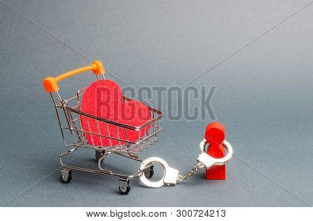 person is handcuffed to a red heart on a supermarket cart. Man is limited in freedom of action. Difficulties in love, non-reciprocal love. Organization of divorce, legal obstacles. Prostitution