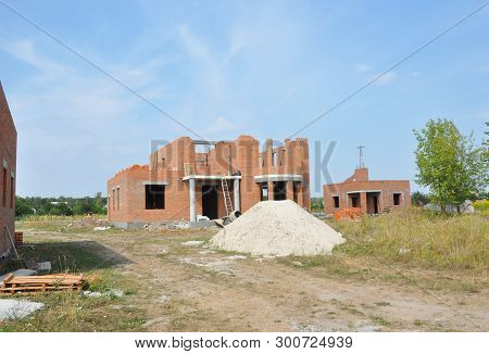 Incomplete Brick House Construction with Doorway Columns and Windows Frame, Pile of Sand poster