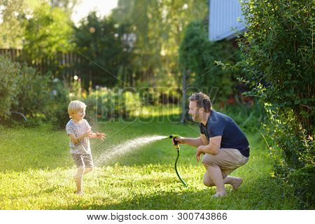 Funny Little Boy With His Father Playing With Garden Hose In Sunny Backyard. Preschooler Child Havin