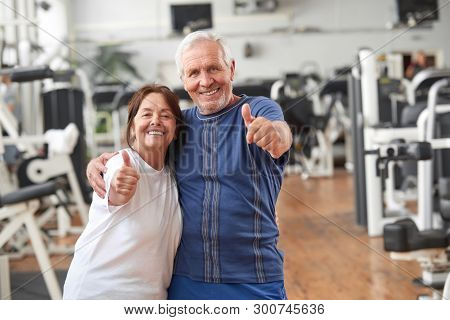 Senior Couple Giving Thumbs Up At Gym. Happy Couple Of Seniors Gesturing Thumbs Up At Fitness Center