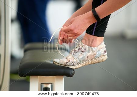 Close Up Woman Tying Sport Shoes. Female Hands Tying Shoelaces At Gym, Side View. Ready For Training