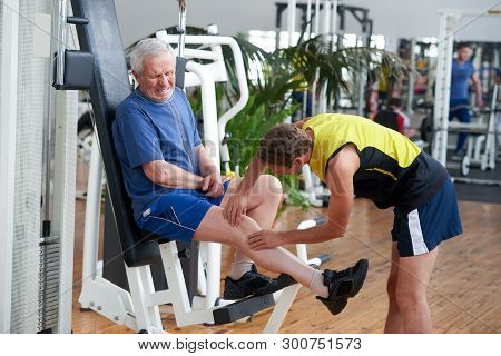 Man Suffering From Knee Pain In Gym. Senior Sportsman Injured Leg When Working Out At Gym. Sport And