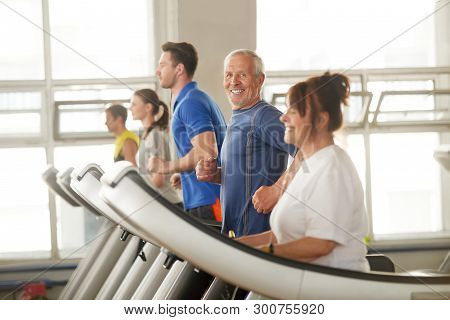 Happy Senior Man Enjoying His Time In Fitness Club. Portrait Of Elderly Man On Treadmill Looking At
