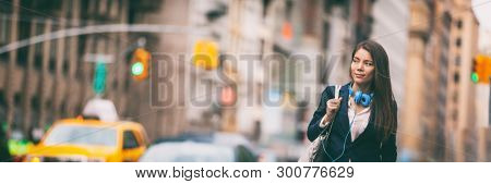 New York City lifestyle Young Asian woman walking commute in NYC street. Urban people hipster girl in traffic banner panorama. Chinese lady looking to side with purse and headphones for commute.
