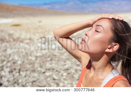 Heat stroke tired dehydrated girl under the desert sun hot temperature summer weather danger. Asian woman sweating exhausted.
